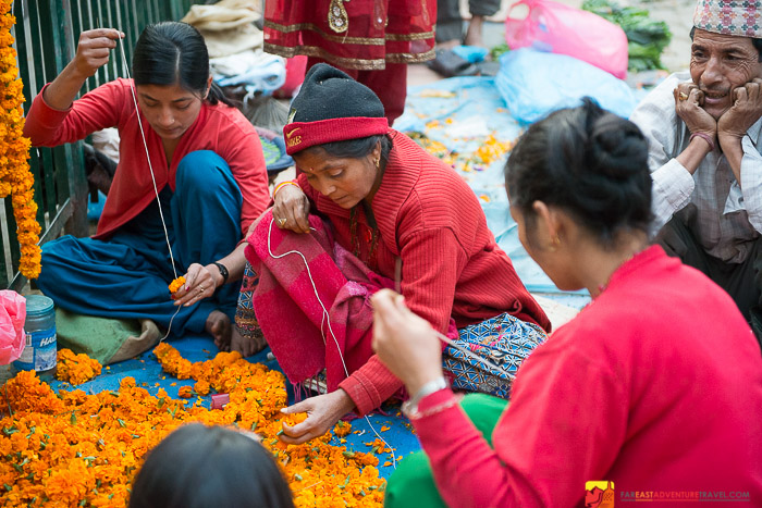 Stringing marigold garlands for temple offerings