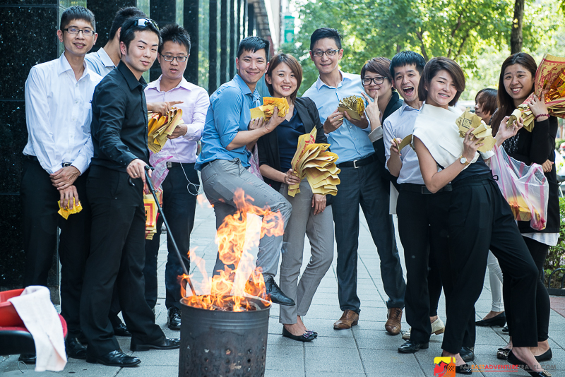 Young business people in the Zhongxiao Dunhua District of Taipei burning paper money to appease the ghosts