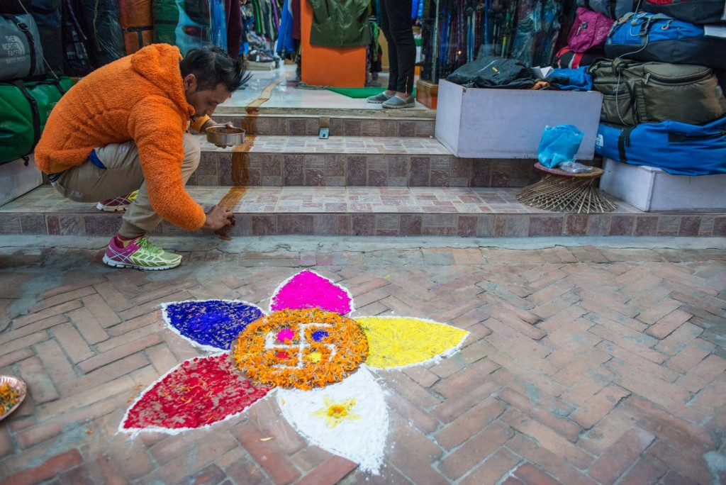 A shop owner in Thamel-Kathmandu, Nepal creates a rangoli art decoration in hopes that the Goddess of Wealth, Lakshmi will pay a visit-during Tihar