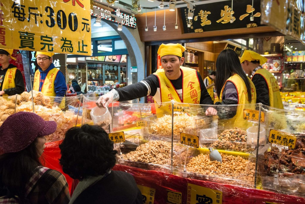 A food seller hands out samples of traditional snacks during the Lunar New Year market on Dihua Street in Taipei, Taiwan