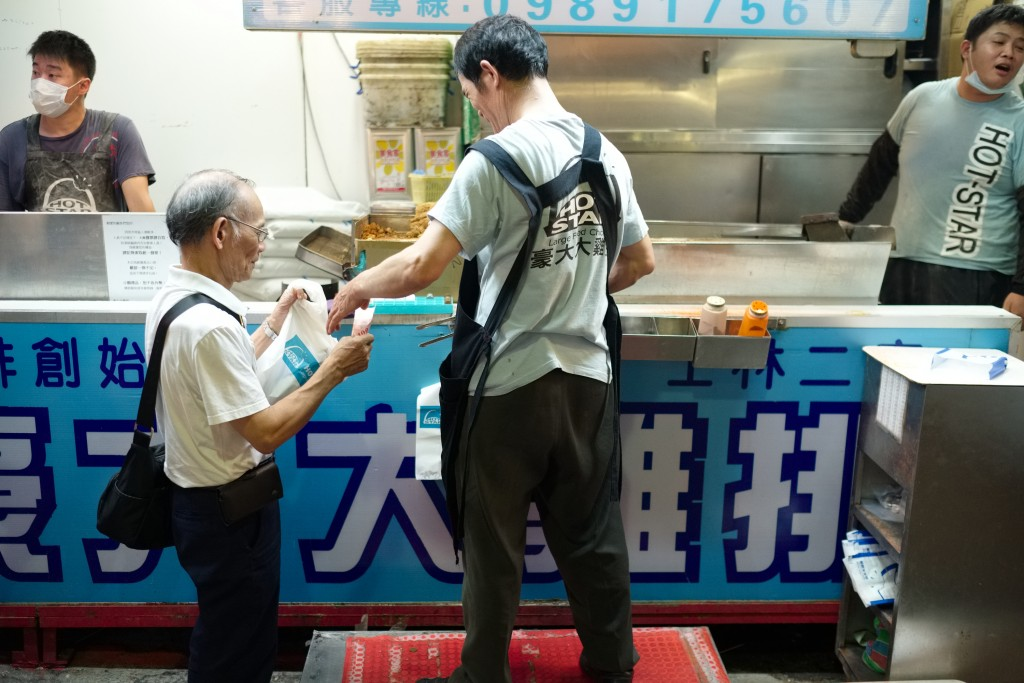 A man receives his order of fried chicken at one of the hundreds of food stalls at Taipei's Shilin Night Market